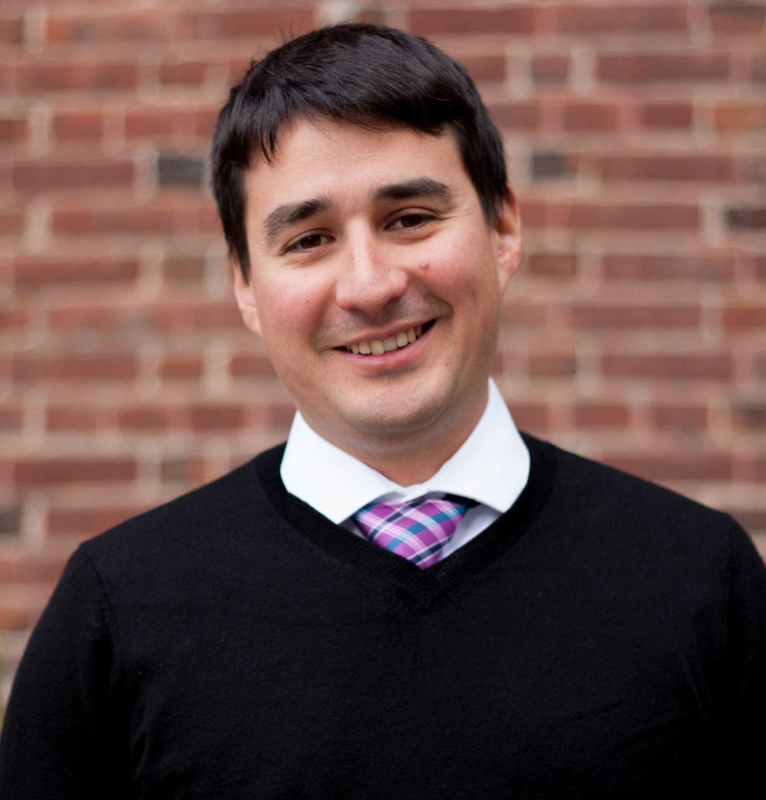 Jesus Barajas with short brown hair, a black shirt and a purple necktie