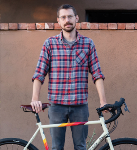 Samuel Jensen, wearing a plaid shirt, stands with a bicycle