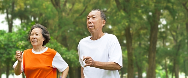 An older couple jogs through a park
