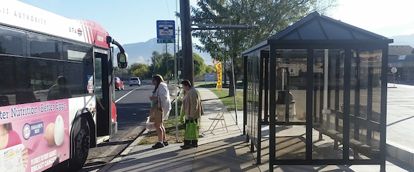 Bus riders board a bus at a stop with a shelter, sign, and benches.