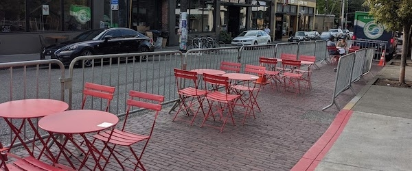 Red restaurant tables and chairs stand in the place of former curbside parking on a Seattle street