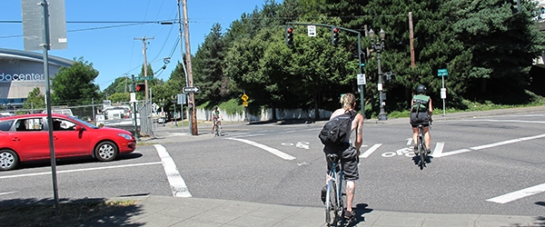 Bicyclists cross an intersection with a bike signal, near a red car