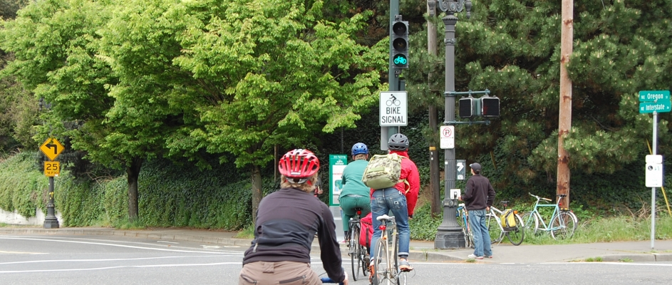 Cyclists riding toward a green bike signal