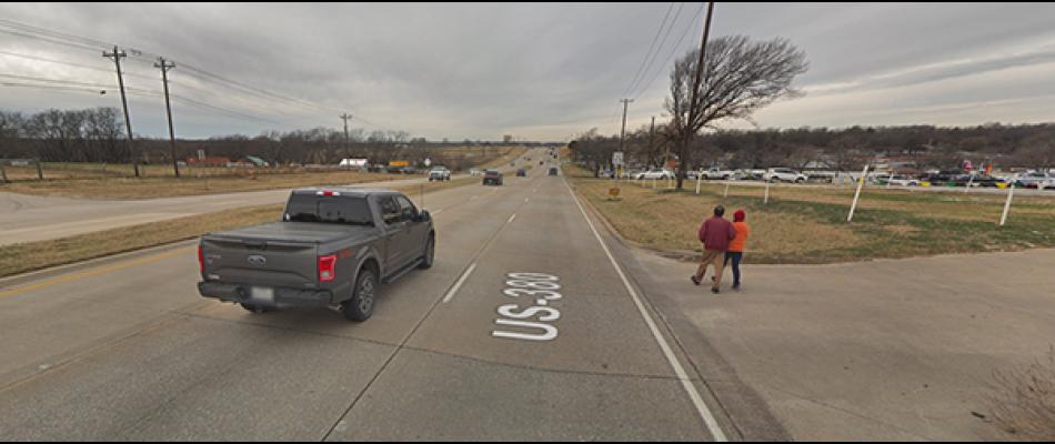 Pedestrians walk along a four-lane road with no sidewalk in Texas.