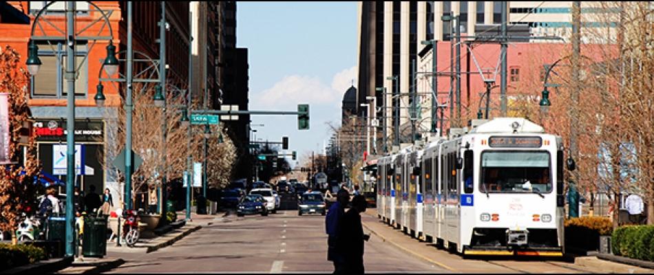 Pedestrians cross near a light rail amid mixed-use development